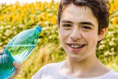 Мальчик с бутылкой воды среди солнцецветов Стоковая Фотография RF
