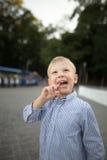 Мальчик с всасывая конфетой идет в парк в лете стоковое изображение rf