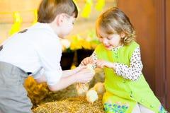 Мальчик с девушкой на сене с цыплятами Стоковое Изображение RF