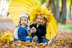 Мальчик с девушкой под зонтиком от осени дождя Стоковые Фотографии RF