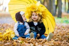 Мальчик с девушкой под зонтиком от осени дождя Стоковые Изображения RF