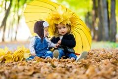 Мальчик с девушкой под зонтиком от осени дождя Стоковые Изображения
