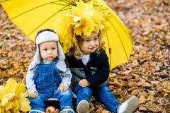 Мальчик с девушкой под зонтиком от осени дождя Стоковое фото RF