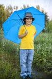 Мальчик с зонтиком outdoors стоковые изображения rf