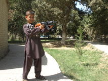 Мальчик с игрушкой автомата Калашниковаа в Balkh, Афганистане стоковые изображения rf