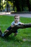 Мальчик с игрушкой в руках лежа на дереве Стоковое Фото