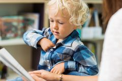 Мальчик с книгой чтения учителя стоковое фото