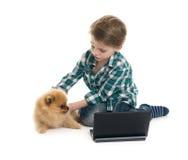 Мальчик с компьтер-книжкой и щенком Стоковая Фотография RF