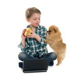 Мальчик с компьтер-книжкой и щенком Стоковая Фотография