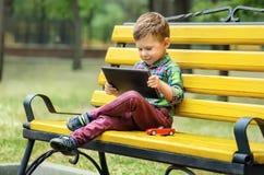 Мальчик с компьютером таблетки Стоковые Изображения
