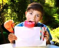 мальчик с конфетой и листом бумаги хлопка стоковые изображения rf