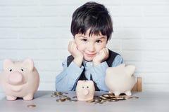 Мальчик с копилкой свиньи Стоковые Фото