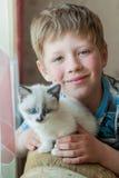 Мальчик с котенком в комнате Стоковое Изображение