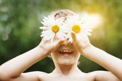 Мальчик с маргариткой наблюдает в парке лета Стоковые Изображения