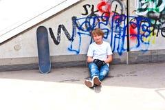 Мальчик с доской конька на парке конька Стоковые Изображения