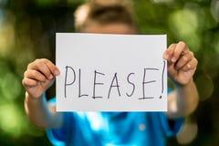Мальчик с пожалуйста подписывает Стоковое фото RF