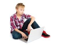 Мальчик с портативным компьютером стоковые изображения rf