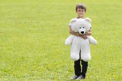 Мальчик с плюшевым медвежонком смотрит камеру Внешний, летний день Скопируйте космос для текста Стоковые Изображения RF