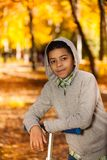 Мальчик с самокатом в парке осени Стоковые Изображения
