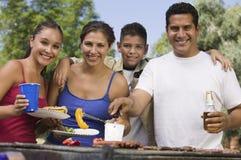 Мальчик (13-15) с семьей на внешнем вид спереди гриля. Стоковые Изображения