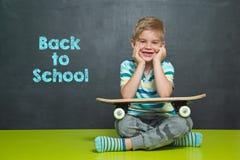 Мальчик с скейтбордом и школьное правление с текстом НАЗАД К ШКОЛЕ Стоковое Изображение