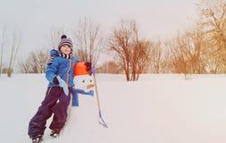 Мальчик с снеговиком в природе зимы Стоковое фото RF