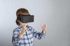 Мальчик с стеклами виртуальной реальности, ребенок пробует новую технологию стоковые фото