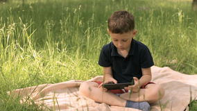 Мальчик с таблеткой в парке на луге видеоматериал