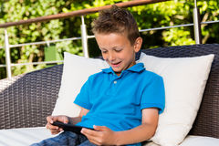 Мальчик с таблеткой на террасе Стоковое Изображение