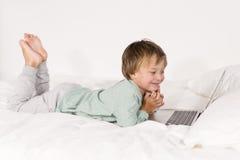 Мальчик с тетрадью лежит на кровати Стоковое Изображение RF