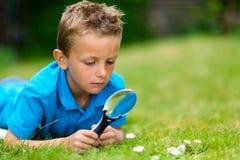 Мальчик с лупой в саде стоковая фотография rf