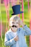 Мальчик с усиком и шляпой смешной бумаги Праздник жизнерадостных детей outdoors Стоковая Фотография RF