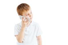 Мальчик слушает музыка и говорит на телефоне с белой предпосылкой Стоковые Фото