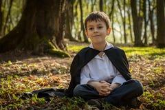 Мальчик с черной накидкой Стоковая Фотография