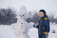 Мальчик с человеком снега Стоковое Фото