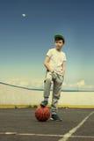 Мальчик с шариком баскетбола на предпосылке неба и луны Концепция спорта Стоковое Изображение RF