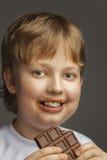 мальчик с шоколадным батончиком стоковая фотография rf