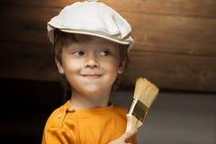 Мальчик с щеткой краски стоковые фото