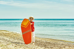 Мальчик с surfboard на взморье Стоковое Изображение