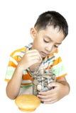 Мальчик Таиланда азиата кладя деньги в стеклянный опарник. Стоковые Изображения