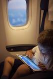 Мальчик тратя время с ПК таблетки во время полета стоковые фото