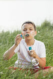 Мальчик дует пузыри мыла Стоковые Изображения