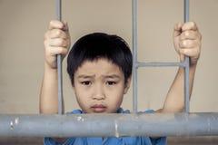 Мальчик унылый за стальным прутом Стоковые Фотографии RF