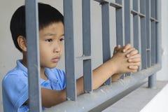 Мальчик унылый за стальным прутом Стоковое Фото