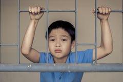 Мальчик унылый за стальным прутом Стоковые Изображения