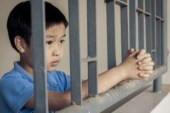 Мальчик унылый за стальным прутом Стоковые Фото