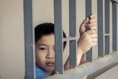 Мальчик унылый за стальным прутом Стоковая Фотография RF