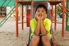 Мальчик унылый на спортивной площадке Стоковое фото RF
