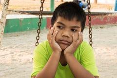 Мальчик унылый на спортивной площадке Стоковые Изображения