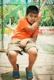 Мальчик унылый самостоятельно на спортивной площадке Стоковое Изображение